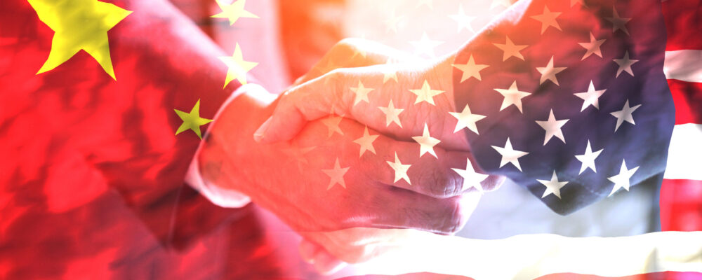 Businessman shake hand over United States of America and China flag.